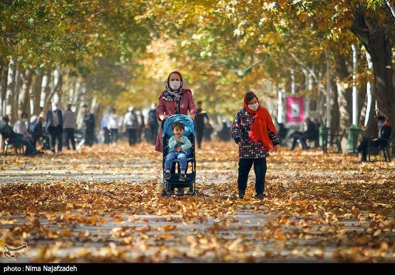 Masked Iranians enjoy the fall foliage in Mashhad