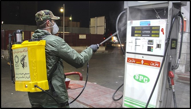 A Basij member disinfects a gas station