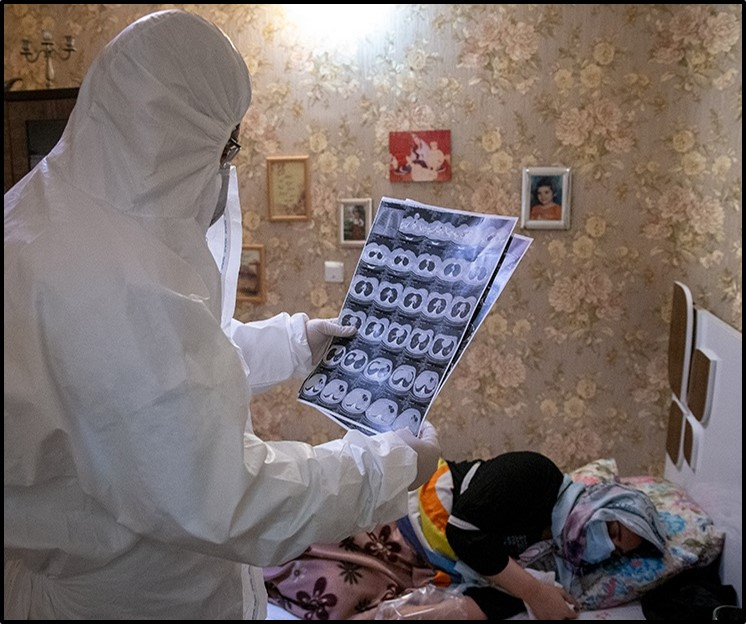 A doctor examines a patient in her home
