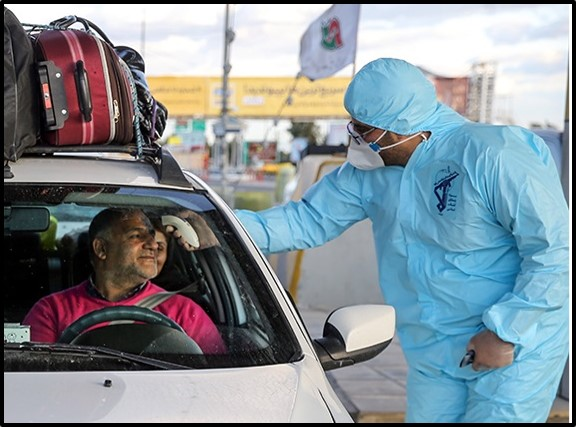 A medical worker checks a driver's temperature on the Qom-Tehran highway