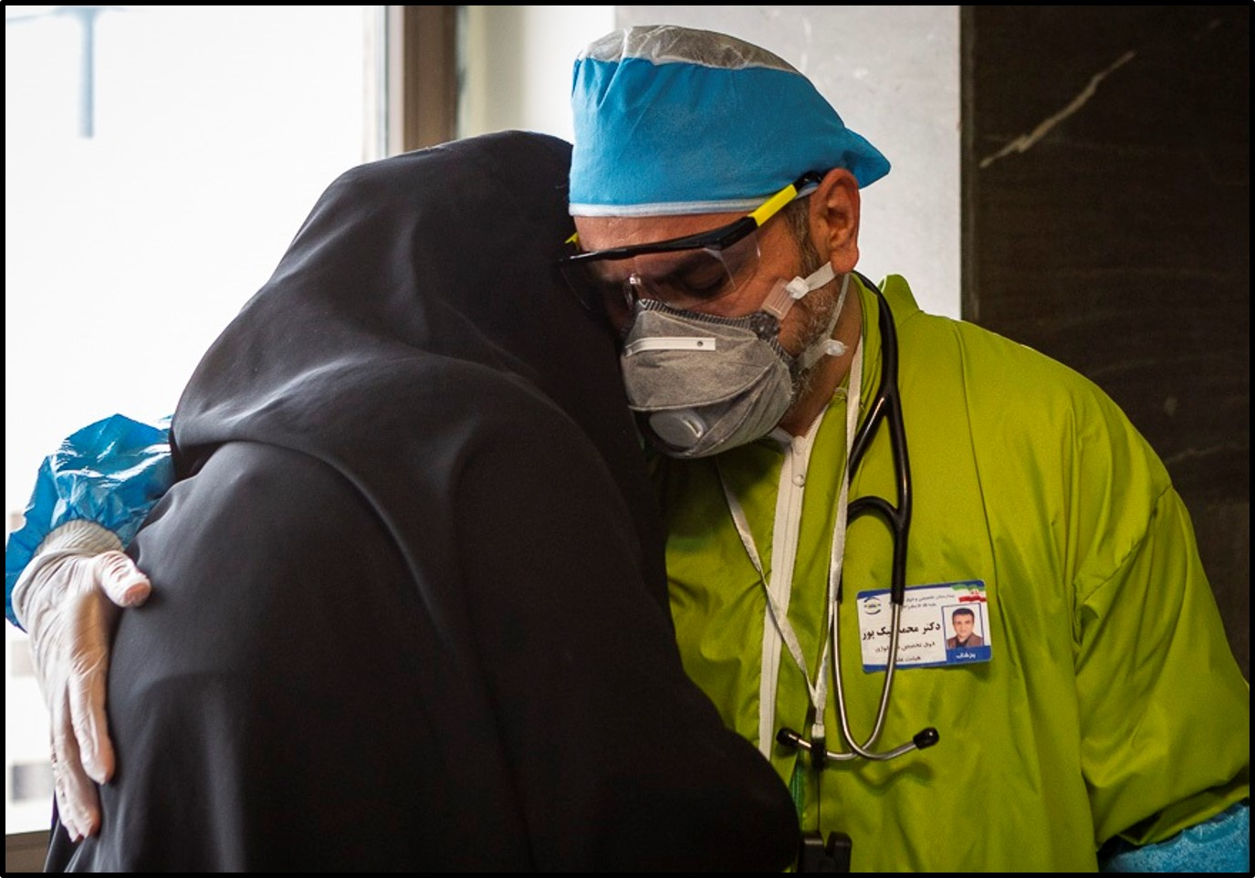 A doctor comforts a woman at a hospital in Tehran